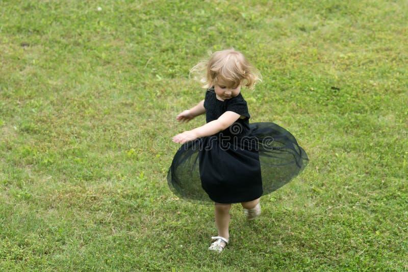 M?dchen mit Drehbeschleunigung des blonden Haares im schwarzen Kleid auf Gras lizenzfreie stockbilder