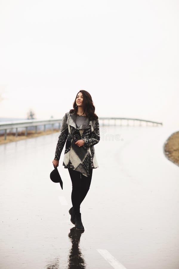 M?dchen mit einem schwarzen Hut gehend entlang die Stra?e an einem regnerischen Tag lizenzfreie stockbilder
