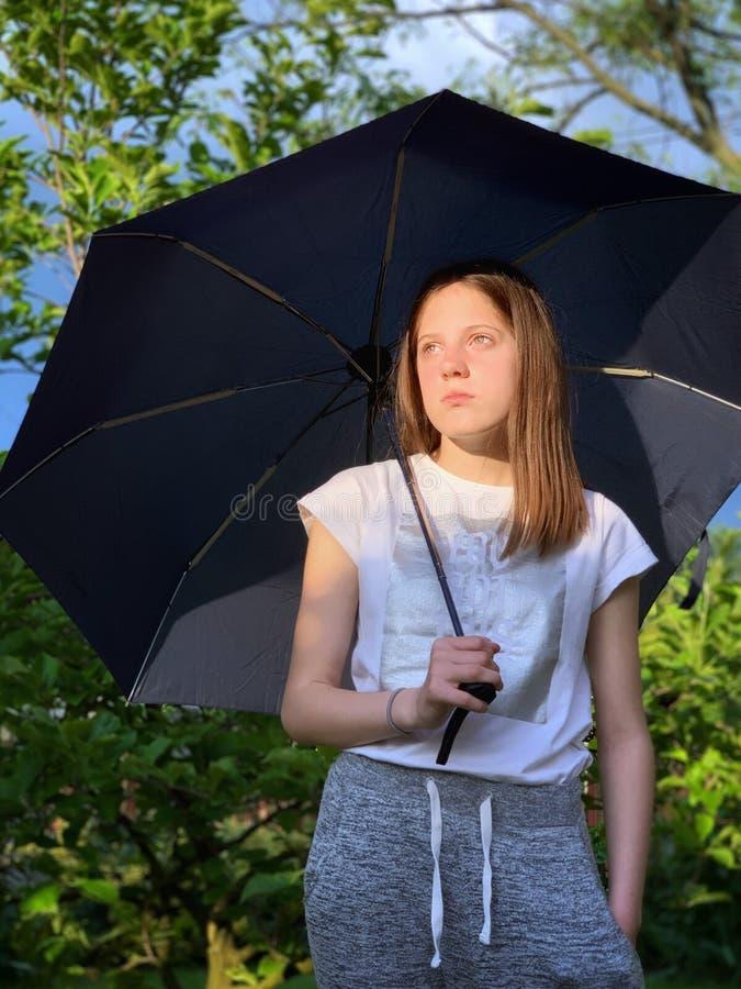 M?dchen mit Regenschirm an einem regnerischen Tag stockfotografie