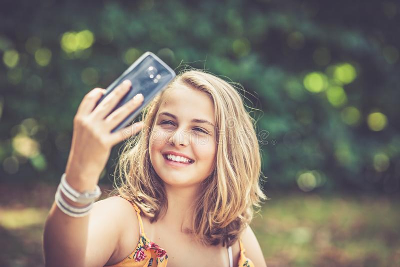 M?dchen mit Smartphone drau?en stockfotografie
