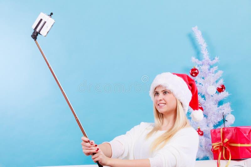 M?dchen in Sankt-Hut, der Foto von unter Verwendung selfie Stockes macht stockfotografie