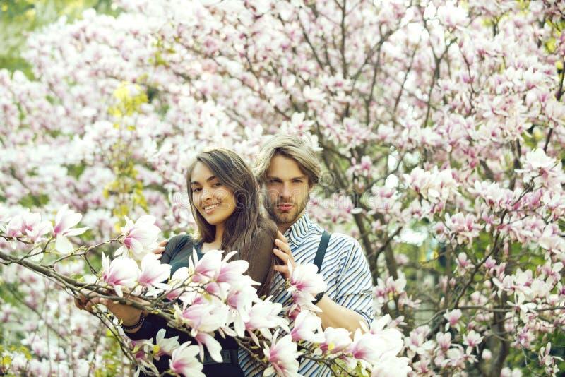 M?dchen und gut aussehender Mann an den Magnolienb?umen lizenzfreie stockfotografie
