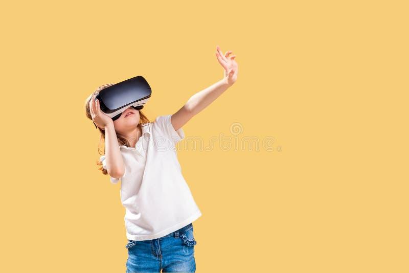M?dchen 7 y O Erfahren des VR-Kopfh?rerspiels auf gelbem Hintergrund r r stockbilder