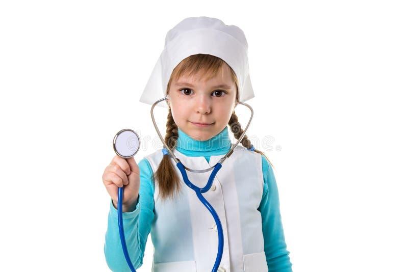 M?dchenkrankenschwester in der wei?en Uniform mit Stethoskop in den Ohren Listens Holdingstethoskop auf dem Vordergrund, entfernt stockfoto