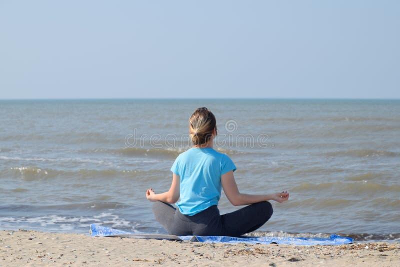 M?dchenpraxisyoga durch das Meer ?bungsgymnastik in der Frischluft durch das Meer lizenzfreies stockbild