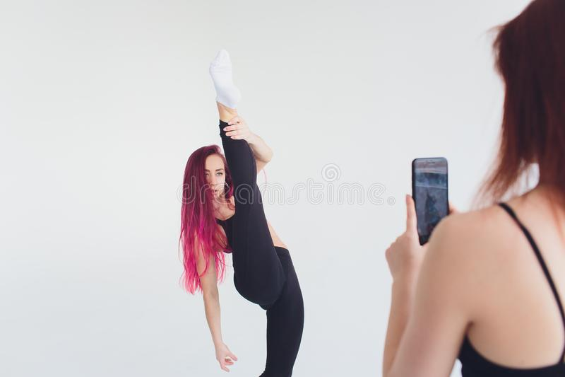 M?dchensporteignungsyoga pilates carimat ?bt Gymnastik Smartphonematte carimat ?bung auf einem beige Hintergrund aus lizenzfreie stockbilder