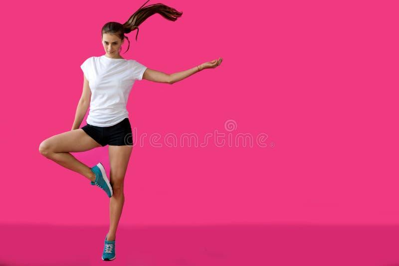 M?dchensportler, der auf einem rosa Hintergrund aufwirft stockbilder