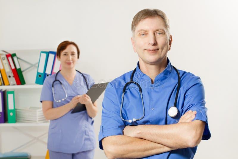 M?decin masculin avec les bras crois?s et docteur f?minin avec le dossier dans le bureau m?dical, assurance-maladie, l'espace de  photos libres de droits