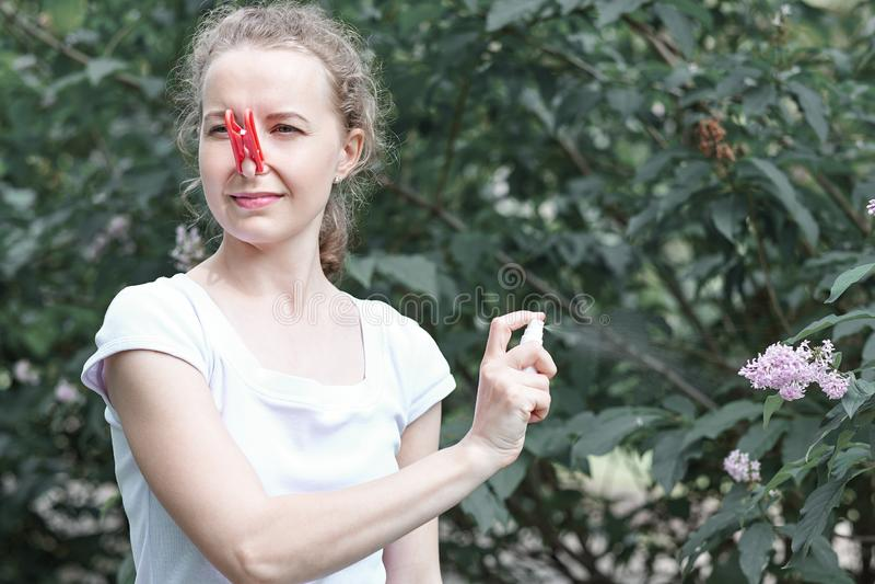 M?decine d'allergie Une femme pulv?rise l'a?rosol sur un buisson des fleurs Pollen, fleur d'été ? Femme protégeant son nez contre photos stock