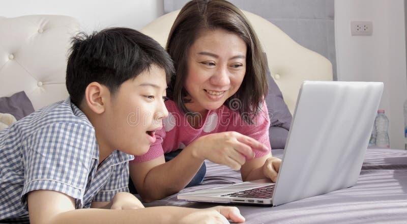 M?e asi?tica e filho da fam?lia que olham no laptop fotografia de stock