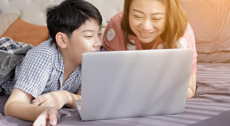 M?e asi?tica e filho da fam?lia que olham no laptop imagem de stock