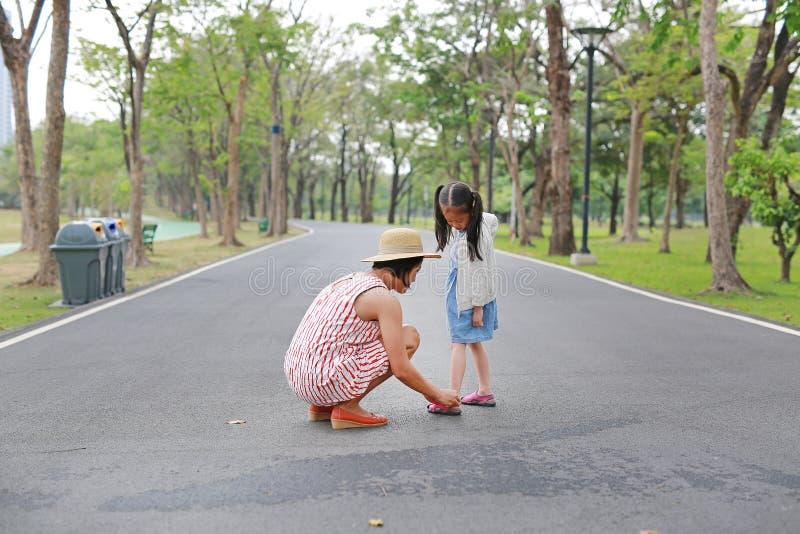 M?e asi?tica que ajuda sua filha pequena a p?r sapatas sobre a estrada exterior fotos de stock