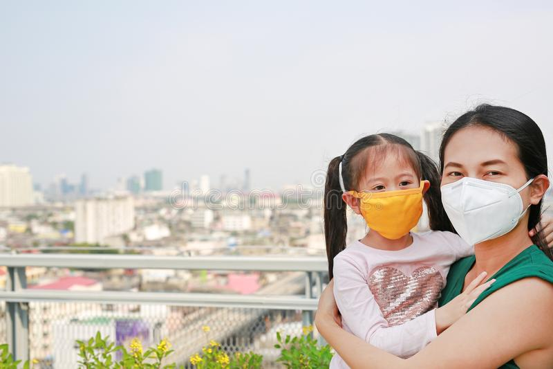M?e asi?tica que leva sua filha com vestir uma m?scara da prote??o contra PM 2 polui??o do ar 5 na cidade de Banguecoque tail?ndi imagens de stock royalty free