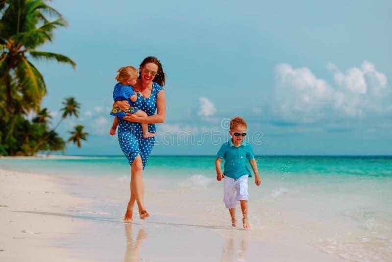 A m?e com crian?as joga a corrida na praia tropical imagem de stock royalty free