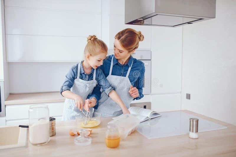M?e com a filha na cozinha imagens de stock royalty free