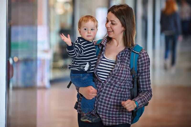 M?e com o beb? dos anos de idade an1 que anda no shopping A m?e guarda o beb? em seus bra?os imagens de stock royalty free