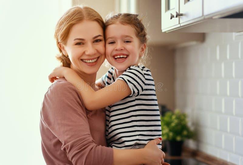 M?e da fam?lia e filha da crian?a que abra?a na cozinha imagens de stock royalty free