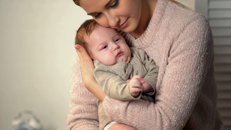 M?e de amor que afaga o beb? pequeno maciamente, cuidados m?dicos e o patroc?nio rec?m-nascidos foto de stock royalty free