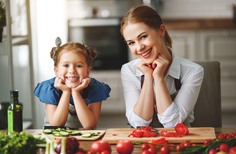 M?e feliz da fam?lia com a menina da crian?a que prepara a salada vegetal foto de stock royalty free