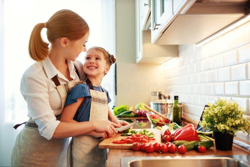 M?e feliz da fam?lia com a menina da crian?a que prepara a salada vegetal imagens de stock royalty free