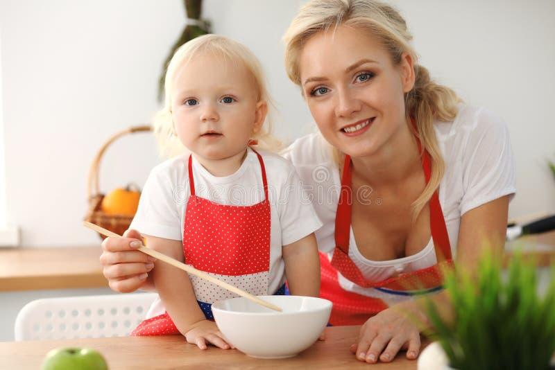 M?e feliz e filha pequena que cozinham na cozinha Tempo todo da despesa junto, conceito do divertimento da fam?lia fotos de stock