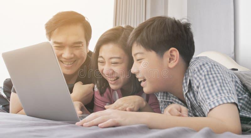 M?e feliz e filho do pai da fam?lia que olham no laptop foto de stock