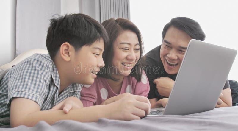 M?e feliz e filho do pai da fam?lia que olham no laptop imagens de stock
