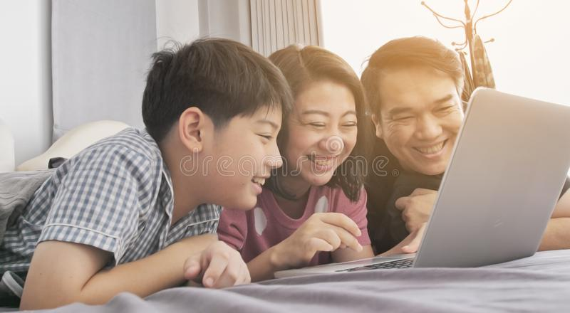 M?e feliz e filho do pai da fam?lia que olham no laptop fotos de stock royalty free