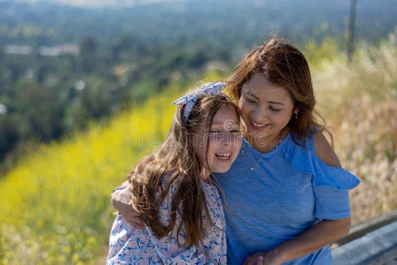 M?e e filha de Latina que sorriem e que riem em um monte na frente das flores amarelas fotografia de stock royalty free