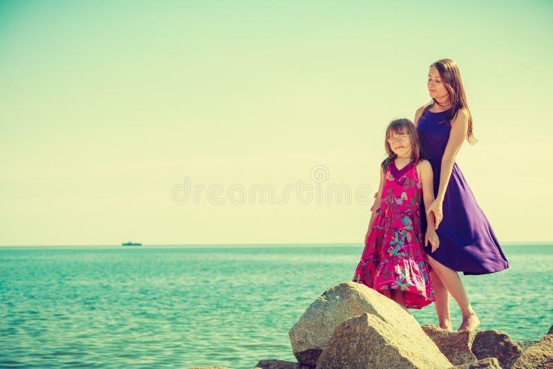 M?e e filha que levantam em rochas do mar fotografia de stock