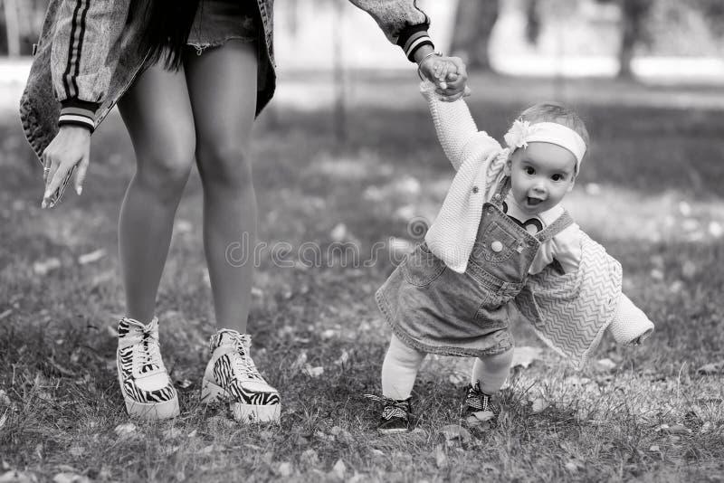 A m?e guarda a m?o da sua filha em um dia de mola no ar fresco, a fam?lia anda no parque e aprecia-se, preto e imagem de stock