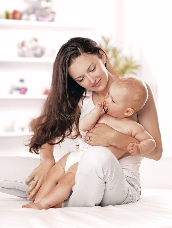 A m?e nova ensina o beb? estar O conceito da maternidade foto de stock royalty free