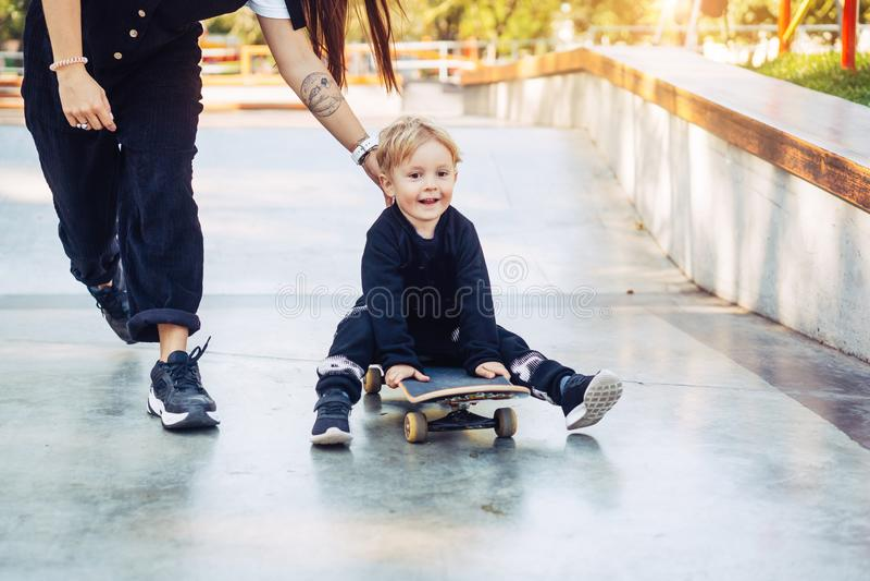 A m?e nova ensina seu rapaz pequeno montar um skate fotografia de stock