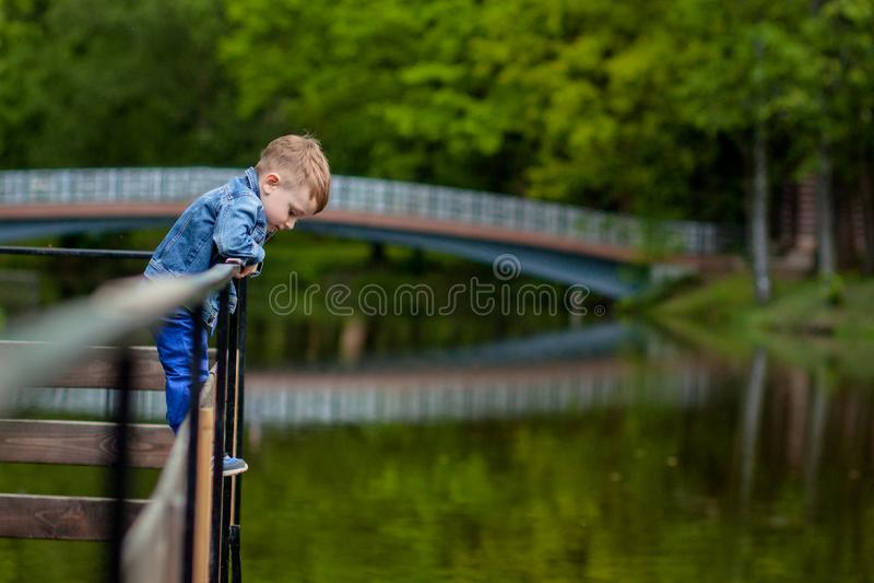 M?e nova feliz que joga e que tem o divertimento com seu filho pequeno do beb? no dia morno da mola ou de ver?o no parque Conceit foto de stock royalty free