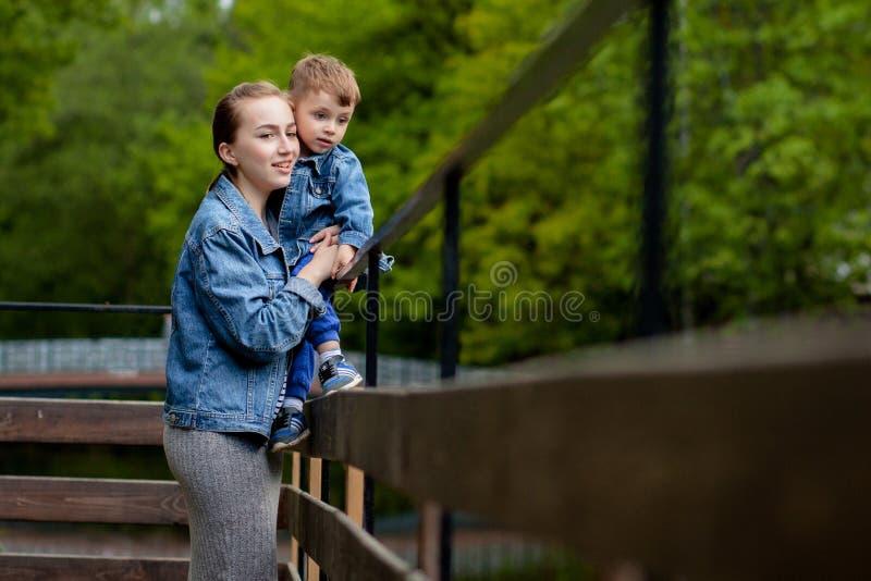 M?e nova feliz que joga e que tem o divertimento com seu filho pequeno do beb? no dia morno da mola ou de ver?o no parque Conceit fotografia de stock