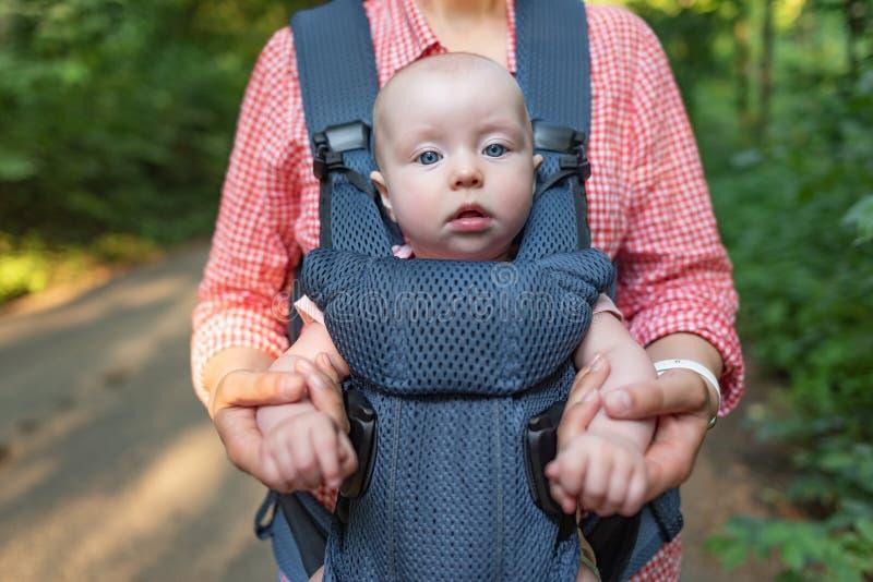 M?e nova e seu beb? em um portador de beb? fotografia de stock