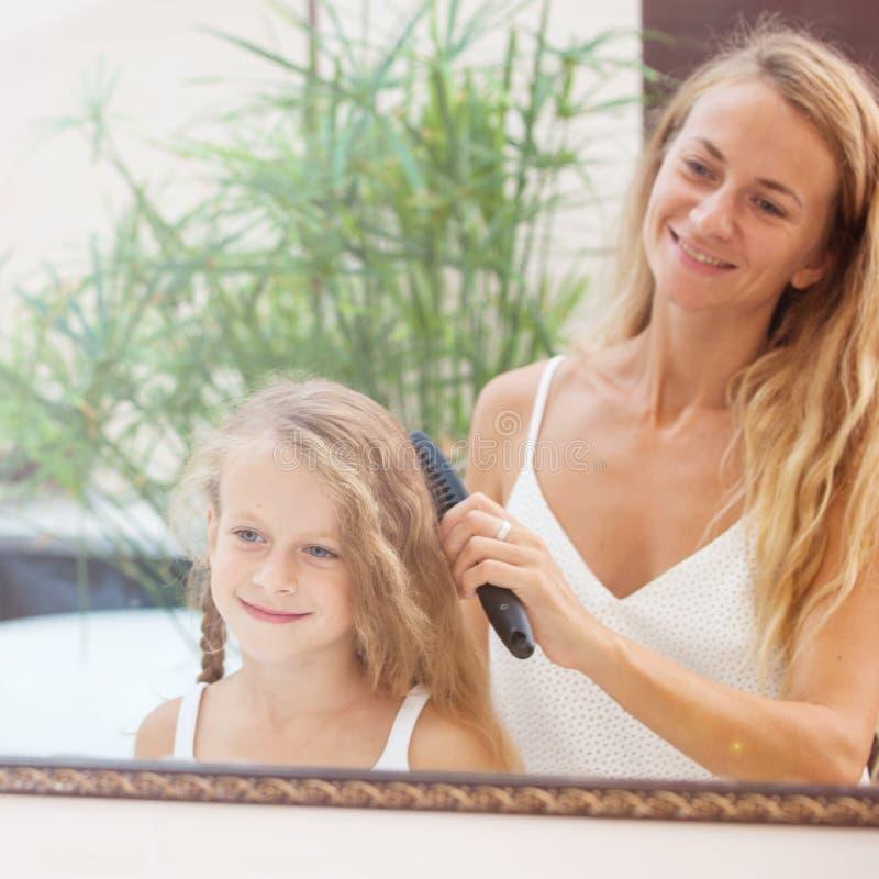 M?e que penteia o cabelo da filha fotografia de stock