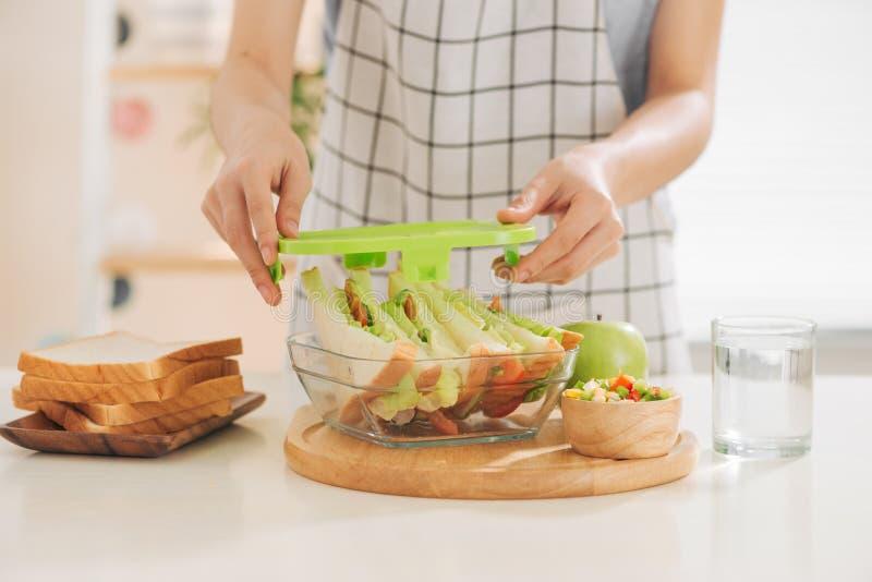 M?e que prepara o sandu?che para o almo?o escolar na tabela foto de stock royalty free
