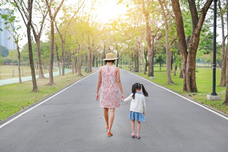 M?e e sua filha que andam na estrada e que guardam as m?os no jardim exterior da natureza Vista traseira imagem de stock royalty free