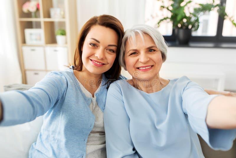 M?e superior e filha adulta que tomam o selfie imagens de stock royalty free