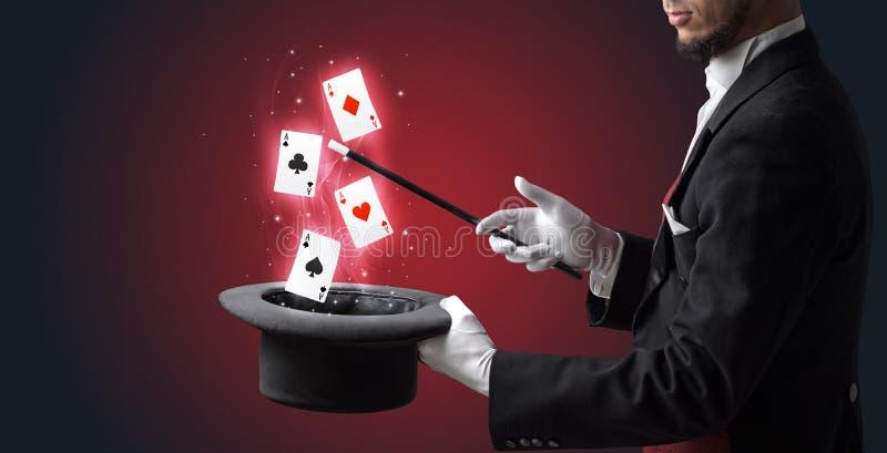 M?gico que faz o truque com os cart?es da varinha e de jogo foto de stock royalty free