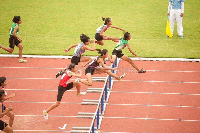 100 m. Hurdles in Thailand Open Athletic Championship 2013. PHATUMTANI,THAILAND – SEPTEMBER,6 : Groups of women player action of 100 m.Hurdles in stock photography