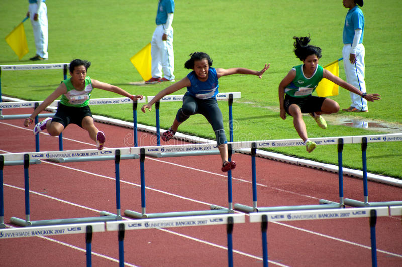 100 m. Hurdles in Thailand Open Athletic Championship 2013. PHATUMTANI,THAILAND – SEPTEMBER,6 : Groups of women player action of 100 m.Hurdles in royalty free stock photo