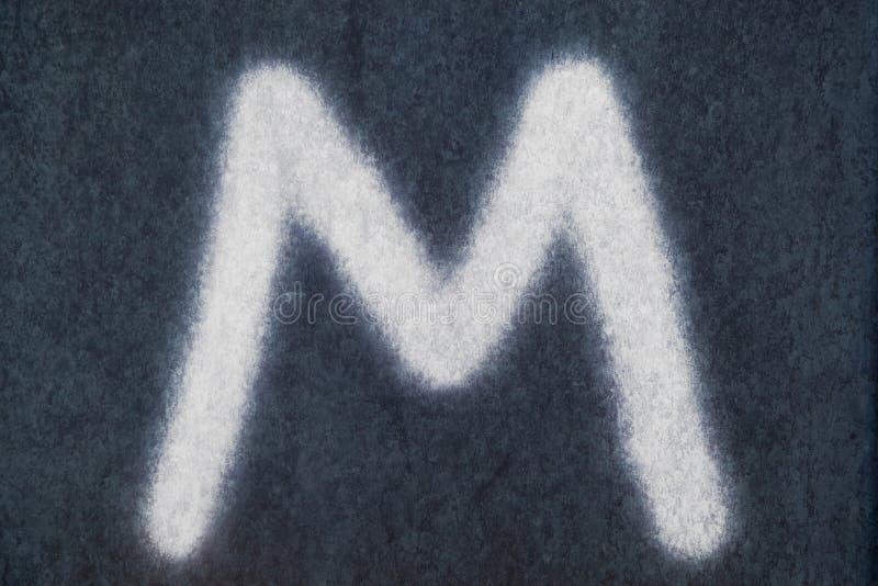 M isolerad kritabokstav i svart tavlabakgrund arkivbilder