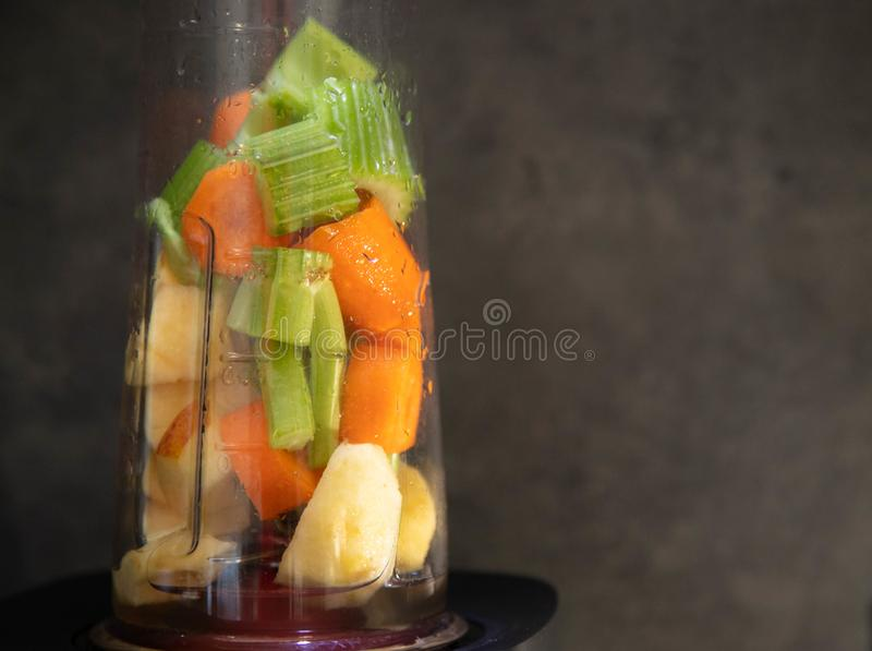 M?langeur avec les l?gumes frais Céleri, pomme et carotte coupés en tranches dans une tasse de mélangeur pour un smoothie Nourrit image stock