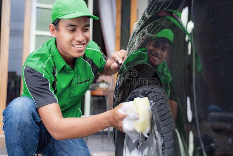 M?le dans l'uniforme nettoyant la voiture de son client photographie stock