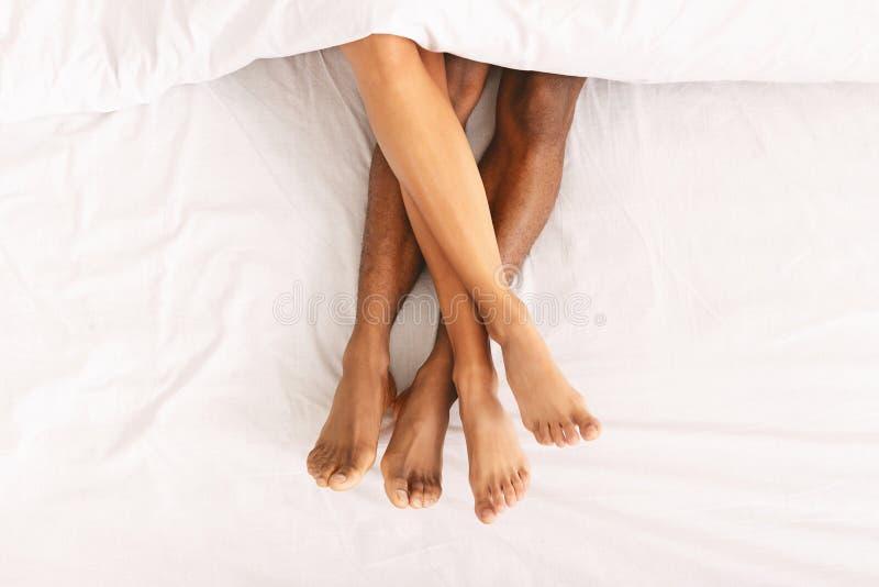 M?le et jambes femelles sous la couette se trouvant sur le lit images stock