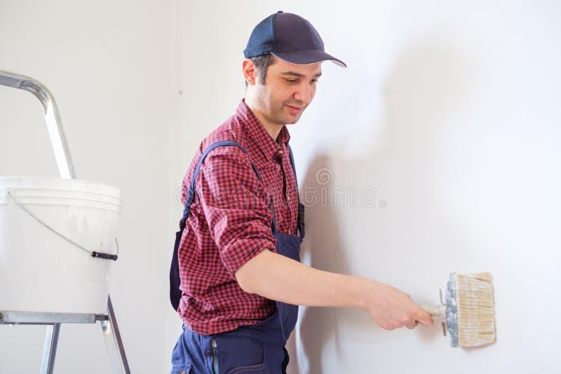 M?le peignant ses murs de maison de blanc avec la brosse photo stock