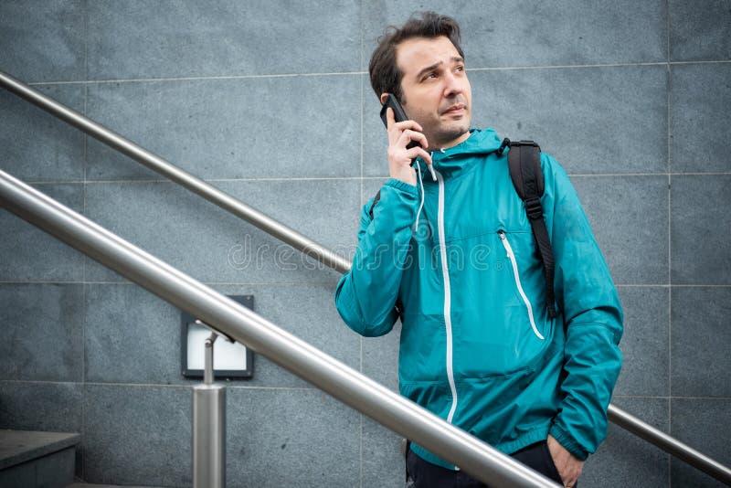 M?le urbain occasionnel ? l'aide du smartphone sur des escaliers photographie stock libre de droits
