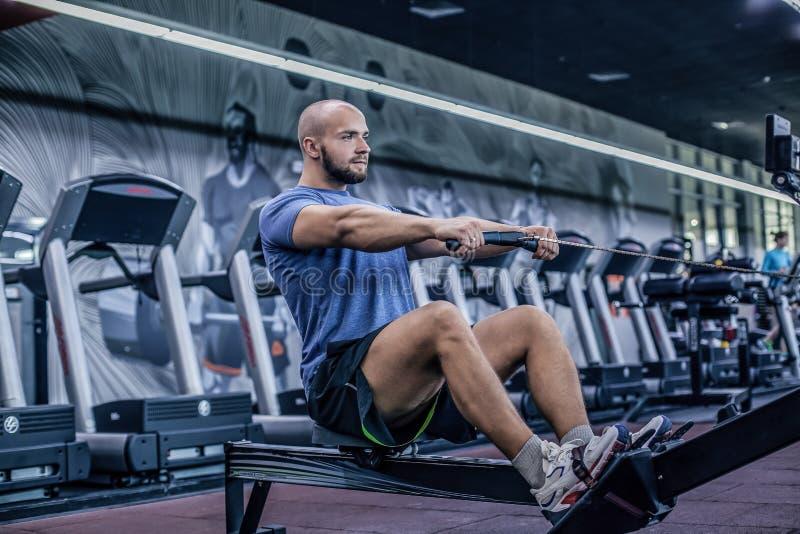 M?le utilisant la machine ? ramer au centre de fitness Jeune homme faisant des exercices sur la machine de forme physique dans le images libres de droits